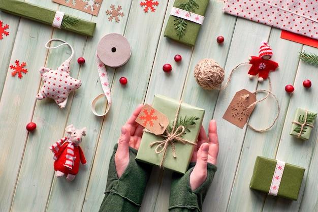 Różne ekologiczne dekoracje świąteczne, zimowe lub noworoczne, zimowe opakowania rzemieślnicze oraz ręcznie robione lub zerowe prezenty. leżał płasko na drewnie, ręce trzymał pudełko ozdobione zielonymi liśćmi.