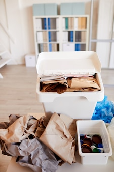 Różne elementy śmieci posortowane według rodzaju materiału i gotowe do recyklingu we wnętrzach biurowych, skup się na koszu na papier na pierwszym planie
