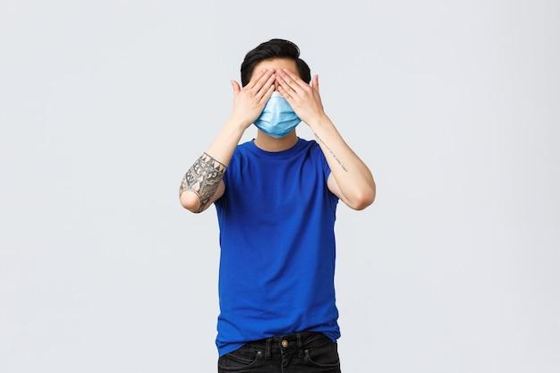 Różne emocje, dystans społeczny, kwarantanna na temat covid-19 i koncepcja stylu życia. azjata w niebieskiej koszulce i masce medycznej stoi z zawiązanymi oczami, zasłania oczy i nie widzi, co się dzieje