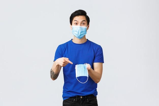 Różne emocje, dystans społeczny, kwarantanna na temat koncepcji koronawirusa i stylu życia. podekscytowany azjata w sprzęcie ochronnym, wskazując palcem na maskę medyczną, zaleca noszenie jej podczas covid-19
