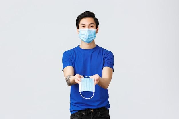 Różne emocje, dystans społeczny, kwarantanna na temat koronawirusa i koncepcji stylu życia. przystojny azjatycki ochotnik płci męskiej, facet w osobistym sprzęcie ochronnym, daje ci maskę medyczną podczas covid-19.