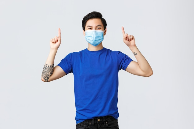 Różne emocje, dystans społeczny, samo-kwarantanna dotycząca koronawirusa i koncepcja stylu życia. rozochocony uśmiechnięty azjatykci mężczyzna w medycznej masce i koszulce, wskazujący palce do reklamować, pokazuje sztandar