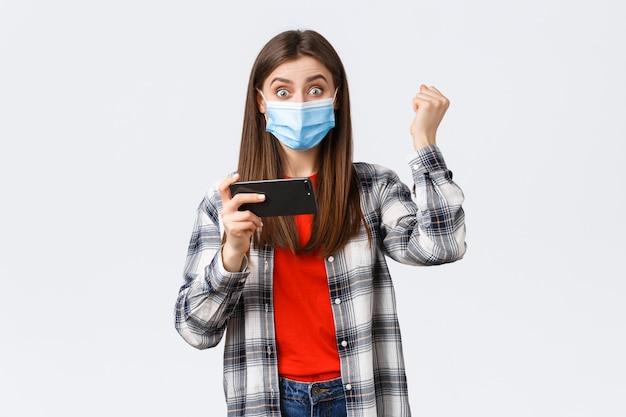 Różne emocje, pandemia covid-19, samo-kwarantanna koronawirusa i koncepcja dystansu społecznego. szczęśliwa dziewczyna w masce medycznej wygrywająca w arcade, pompka pięściowa, przechodząca poziom gry na telefonie komórkowym