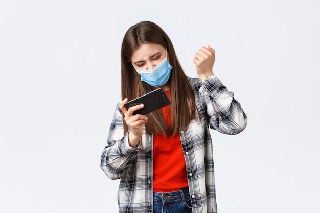 Różne emocje, pandemia covid-19, samo-kwarantanna koronawirusa i koncepcja dystansu społecznego. zadowolona rozradowana kobieta przeszła poziom, pompka pięścią jako wygrana w grze mobilnej, powiedz tak.
