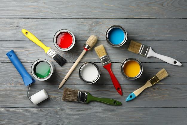 Różne farby, pędzle i rolki na drewnianym stole, widok z góry