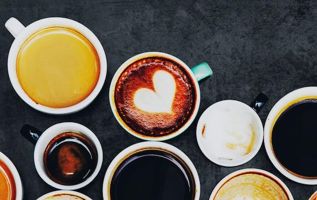 Różne filiżanki do kawy na teksturowanym tle