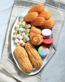 Różne francuskie ciasto na białym marmurowym stole na tekst lub przepis. makaroniki, beza, madeleine, craquelin eclair, mini croissant, duże ciasteczka czekoladowe
