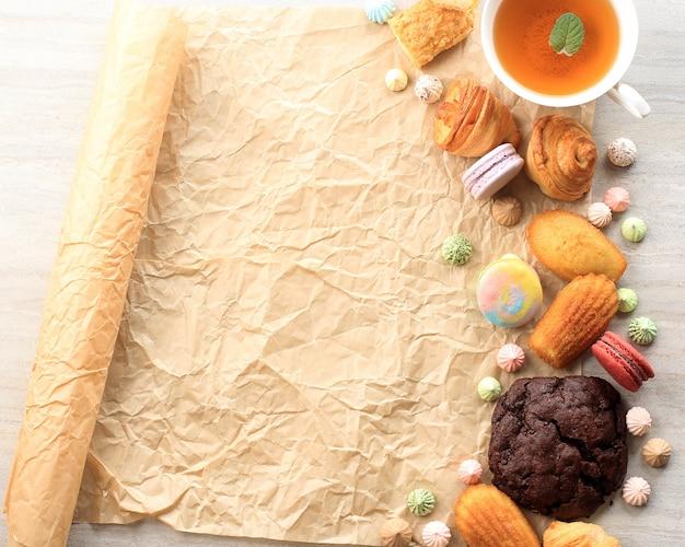 Różne francuskie ciasto na białym marmurowym stole na tekst lub przepis. makaroniki, beza, madeleine, craquelin eclair, mini rogalik, duże ciasteczka czekoladowe, miejsce na tekst
