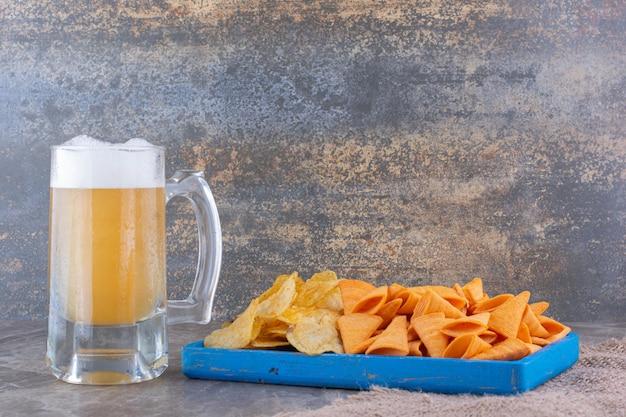 Różne frytki na niebieskim talerzu z piwem