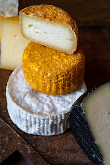 Różne główki sera na desce do krojenia na drewnianym stole. fabryka sera i sklep z serami. naturalne produkty mleczne z gospodarstw rolnych. reklama i menu.