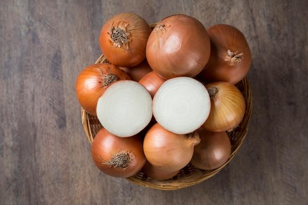 Różne gospodarstwa świeże cebule na rustykalnym drewnianym stole z dymką