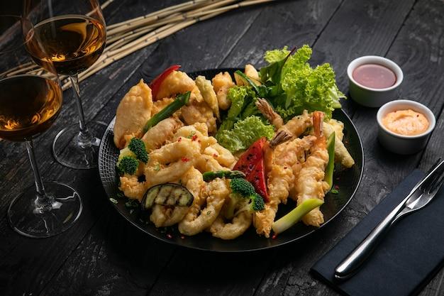 Różne grillowane owoce morza z sosem i białym winem na czarnym stole