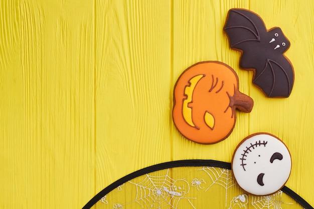 Różne halloweenowe ciasteczka na żółtym tle halloweenowe świąteczne ciasteczka cukrowe, w tym ba...
