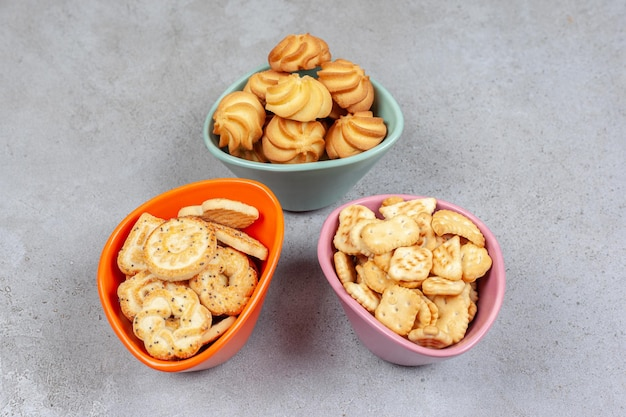 Różne herbatniki i ciasteczka w kolorowych miskach na marmurowej powierzchni.