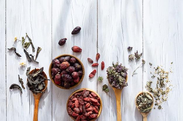 Różne herbaty ziołowe w drewnianych łyżkach na białym drewnianym stole
