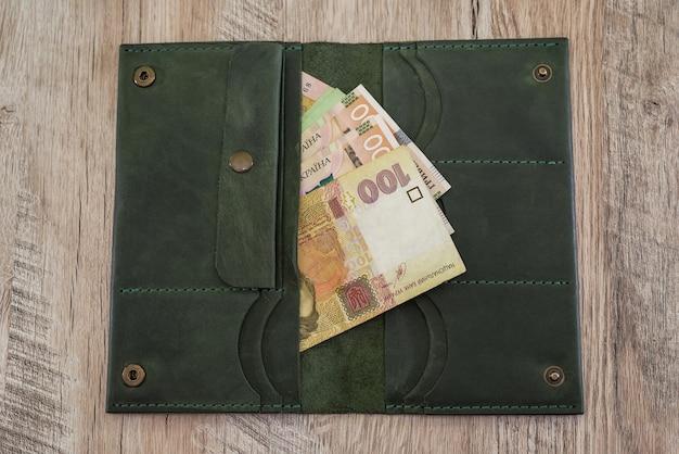 Różne hrywny w portfelu kobiety na drewnianym stole. koncepcja finansowa.