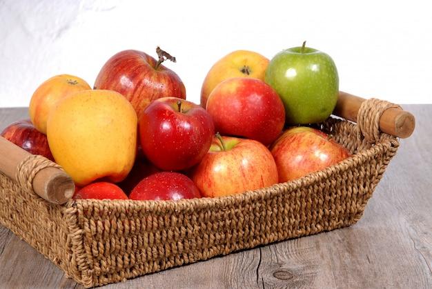 Różne jabłka w wiklinowym koszu