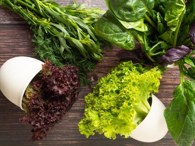 Różne jadalne świeże zioła, zielenie zieleni i fioletu w białych doniczkach i na drewnianym stole, widok z góry,