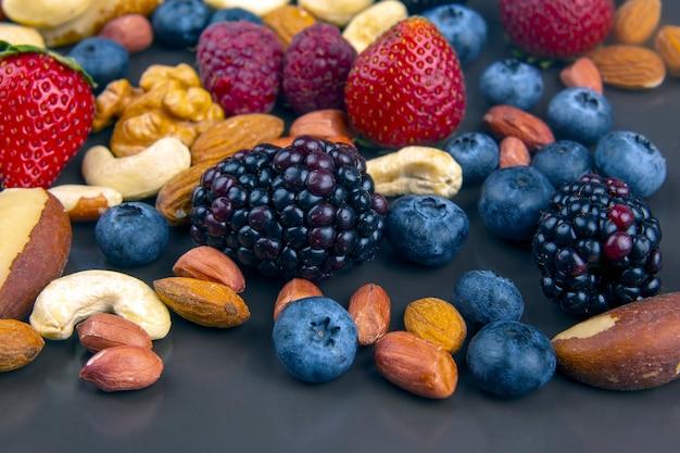 Różne jagody i orzechy na talerzu. białka witaminowe i zdrowa żywność
