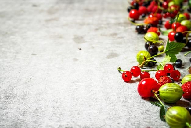Różne jagody na starym kamiennym stole.