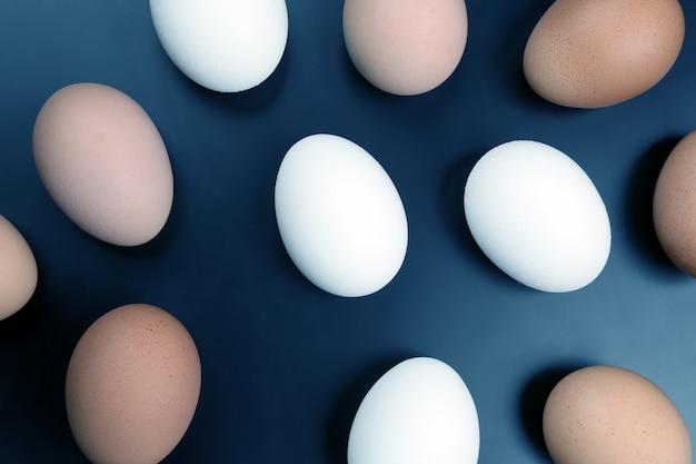 Różne jaja kurze leżą na ciemnym tle