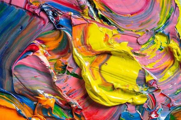 Różne jasne kolory farb olejnych są mieszane na zbliżeniu palety.