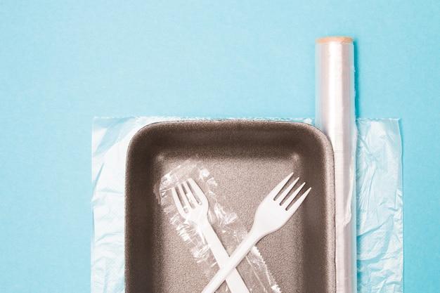 Różne jednorazowe plastikowe opakowania na niebieskim tle, taca na żywność, rolka plastikowej taśmy i torba do zamrażania żywności, jednorazowy widelec i rurka do picia, koncepcja zanieczyszczenia środowiska