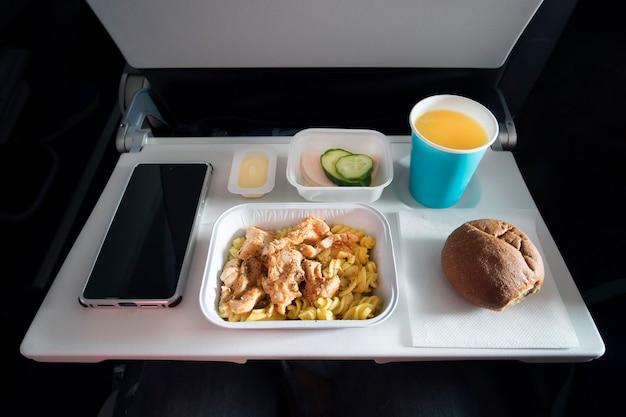 Różne jedzenie klasy ekonomicznej i smartfon pasażera z pustym ekranem na składanym stole samolotu. posiłki na pokładzie samolotu. plastikowe sztućce nóż i widelec w talerzu z jedzeniem.