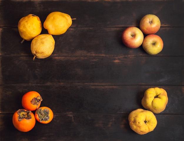 Różne jesienne owoce leżą na rogach drewnianego tła z miejscem na kopię.