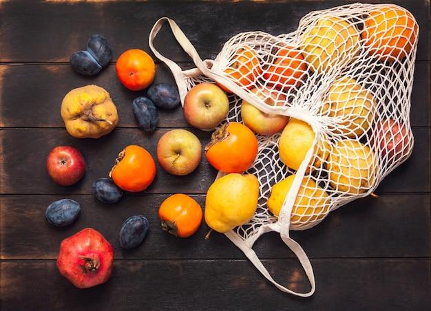 Różne jesienne owoce w siatkowej torbie na ciemnym tle drewnianych.