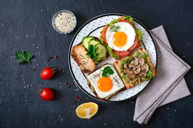 Różne kanapki na czarnym stole. smaczna zdrowa przekąska z awokado. szybkie śniadania. koncepcja zdrowego odżywiania. odpowiednie odżywianie. widok z góry