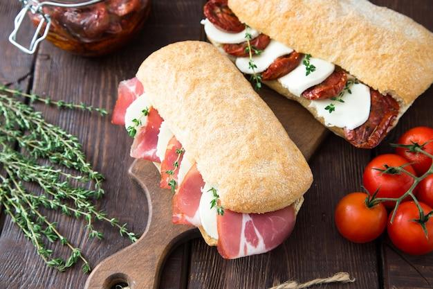 Różne kanapki. sandwich caprese z mozzarellą i suszonymi pomidorami oraz ciabatta z szynką