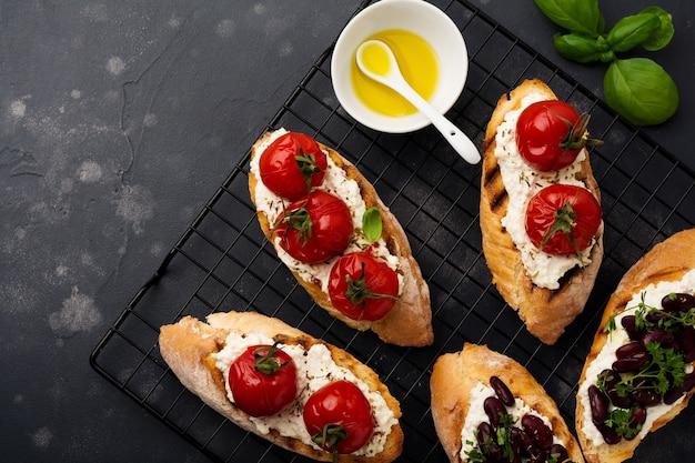 Różne kanapki z czerwoną fasolą, pieczonymi pomidorkami koktajlowymi, czosnkiem, oliwą z oliwek i twarogiem na ciemnej powierzchni