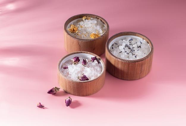 Różne kąpielowe sole w drewnianym talerzu na różowym tle. promienie słoneczne. pojęcie zabiegów spa, pielęgnacji skóry. olejki eteryczne i suszone kwiaty róży, lawenda. społeczna odpowiedzialność za środowisko.