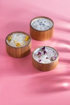 Różne kąpielowe sole w drewnianym talerzu na różowym tle. promienie słoneczne. pojęcie zabiegów spa, pielęgnacji skóry. olejki eteryczne i suszone kwiaty róży, lawenda.