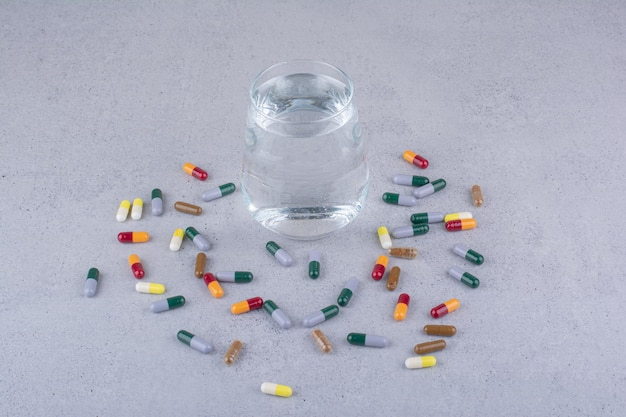 Różne kapsułki farmaceutyczne i szklanka wody. zdjęcie wysokiej jakości