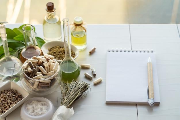 Różne kapsułki z suplementami diety, składnikami do ich tworzenia oraz notes z długopisem.