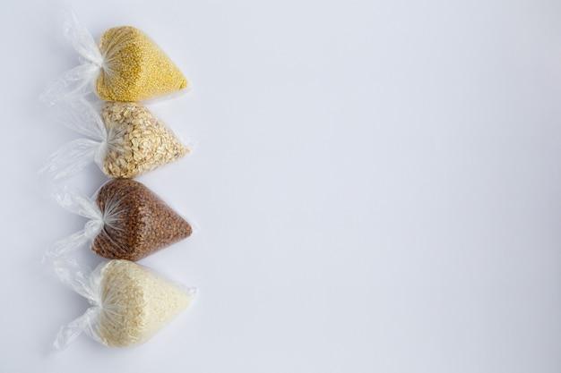 Różne kasze w małych plastikowych torebkach ryż i płatki owsiane gryczana i jaglana
