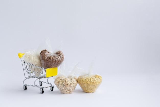 Różne kasze w opakowaniach w koszyku na białym tle. ryż i płatki owsiane, kasza gryczana, proso