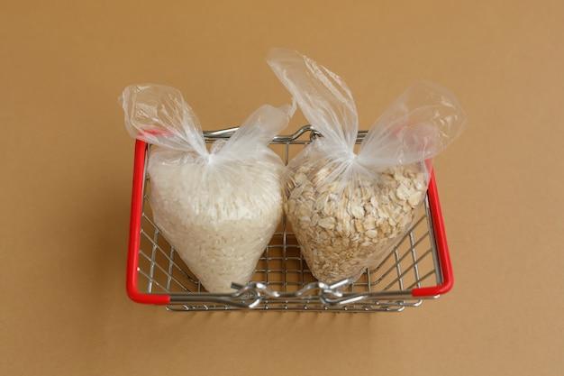 Różne kasze w opakowaniach w koszyku spożywczym ryż i płatki owsiane