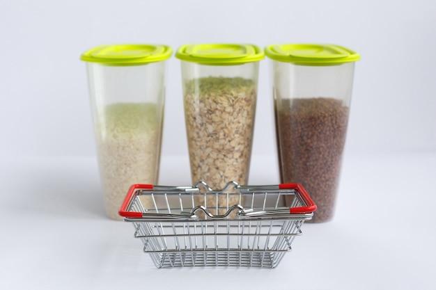 Różne kasze w pojemnikach lub słoiczkach na białej powierzchni oraz mały koszyk spożywczy. ryż, płatki owsiane i gryka