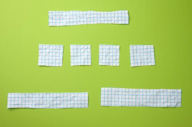 Różne kawałki białego papieru w niebieskiej klatce na zielonej powierzchni. powierzchnia do napisów