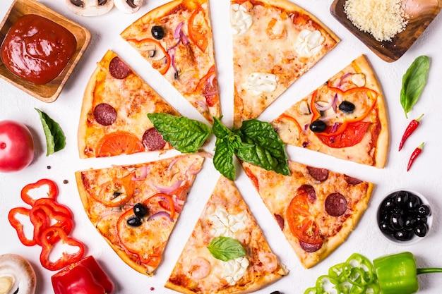 Różne kawałki pizzy na białym tle i składnikach pepperoni pizza wegetariańska i z owocami morza