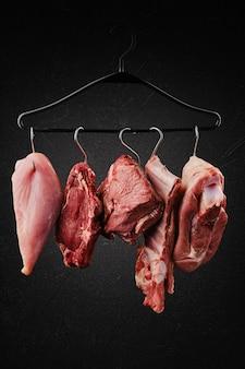 Różne kawałki surowego mięsa na haczyku na wieszaku na czarnym tle