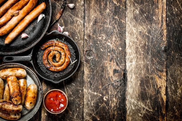Różne kiełbaski w patelniach z sosem pomidorowym na drewnianym stole.