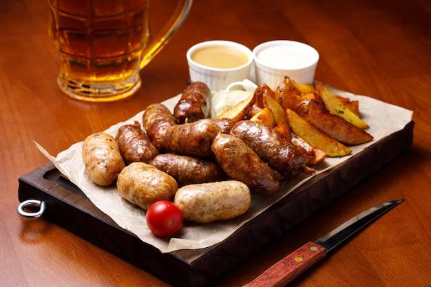 Różne kiełbasy i smażone ziemniaki z sosem z piwem.