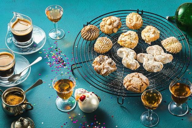 Różne klasyczne włoskie ciasteczka migdałowe domowej roboty z kawą espresso i szklankami słodkiego likieru na stole, świąteczny wystrój