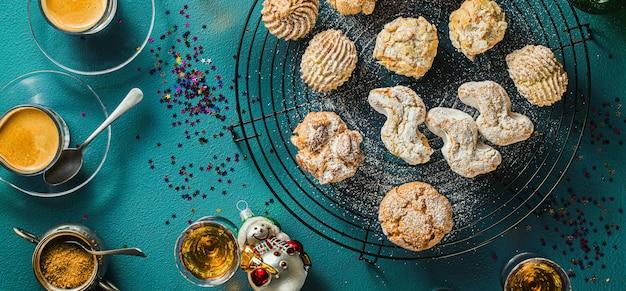 Różne klasyczne włoskie ciasteczka migdałowe domowej roboty z kawą espresso i szklankami słodkiego likieru na stole