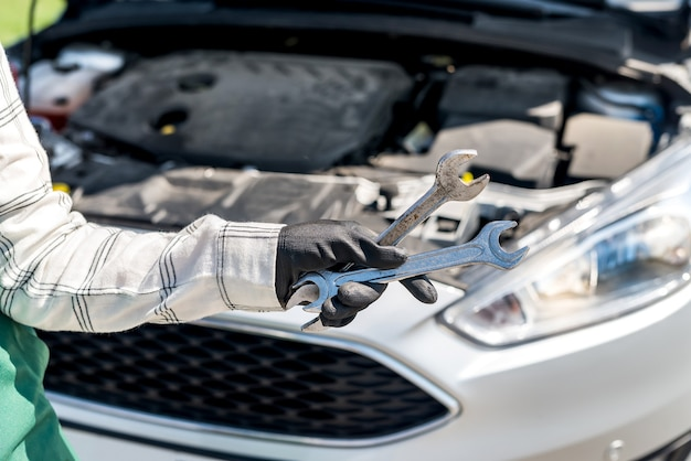 Różne klucze i klucze w ręku nad silnikiem samochodowym