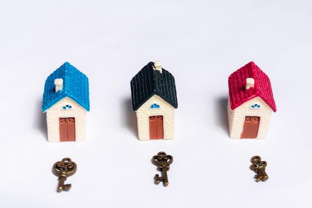 Różne klucze i mały domek na białym tle, pojęcie nieruchomości